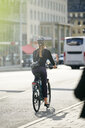 Full length rear view of young female commuter cycling on street in city - MASF12332