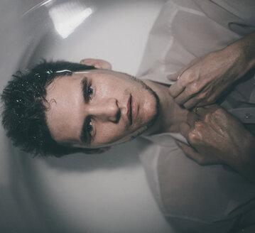 Caucasian man wearing shirt laying underwater in bathtub - BLEF01265
