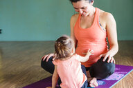 Mixed Race girl touching belly of expectant mother on exercise mat - BLEF01286