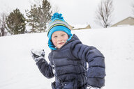 Smiling boy throwing snowball in winter - BLEF01298