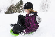 Smiling girl sliding on toboggan in snow - BLEF01301