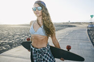 Caucasian woman standing on path at beach with skateboard - BLEF01322