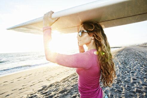 Caucasian woman carrying surfboard on beach - BLEF01325