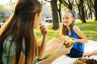 Smiling Caucasian sisters eating food at picnic - BLEF01403