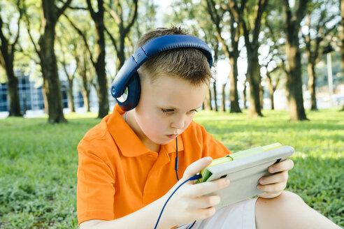 Serious Caucasian boy listening to digital tablet in park - BLEF01436