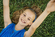 Close up portrait of smiling Caucasian girl laying on grass - BLEF01442