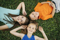 Close up portrait of smiling Caucasian brother and sisters laying on grass - BLEF01445