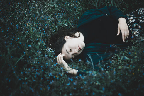Caucasian woman laying in field of wildflowers - BLEF01517