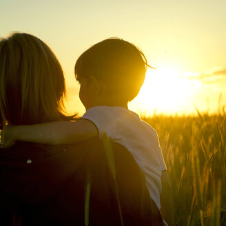 Mother carrying son in field of wheat at sunset - BLEF01619