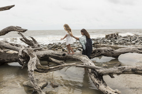 Caucasian mother and daughter walking on driftwood on beach - BLEF01646