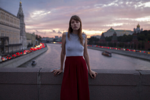 Caucasian woman leaning on bridge over urban canal - BLEF01694