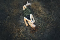 Pensive Caucasian woman laying on grass - BLEF01715