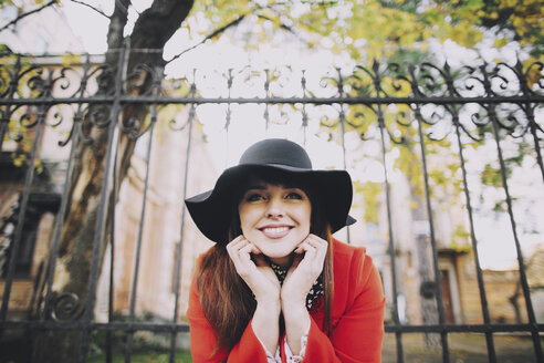 Portrait of smiling Caucasian woman wearing hat near fence - BLEF01718