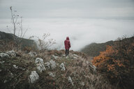 Distant Caucasian woman watching fog on ocean - BLEF01721