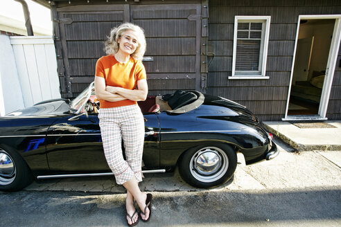 Portrait of older Caucasian woman leaning on convertible car - BLEF01751