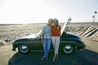 Older Caucasian couple leaning on convertible car with surfboard on beach - BLEF01754