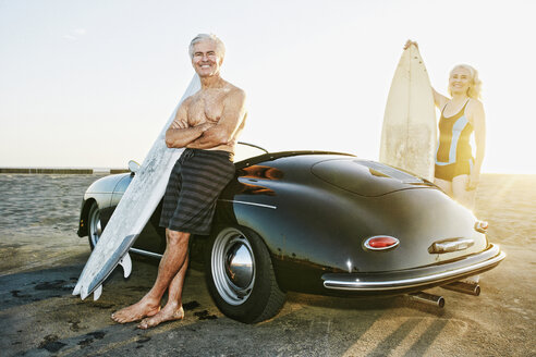 Older Caucasian couple on standing near convertible car with surfboards - BLEF01757