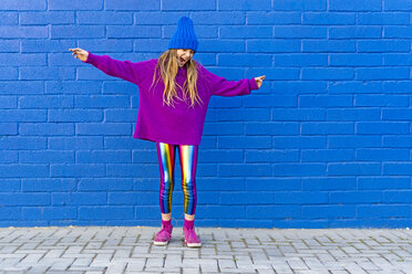 Girl wearing blue cap and oversized pink pullover standing in front of blue wall singing - ERRF01197