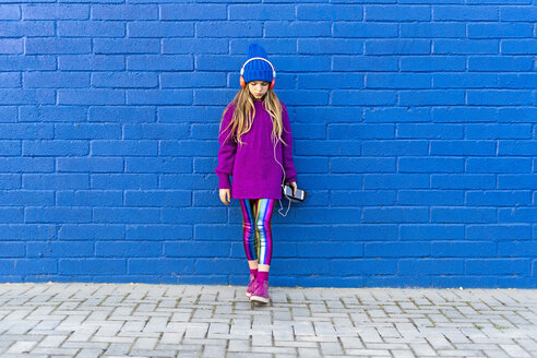 Girl wearing blue cap and oversized pink pullover standing in front of blue wall listening music with headphones - ERRF01200