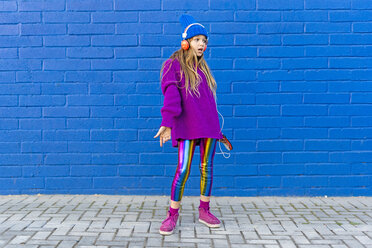 Girl wearing blue cap and oversized pink pullover standing in front of blue wall listening music with headphones - ERRF01203