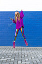 Happy girl with headphones and smartphone jumping in the air in front of blue wall - ERRF01206