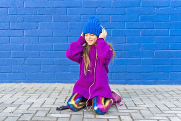 Girl wearing blue cap and oversized pink pullover listening music with headphones in front of blue wall - ERRF01209