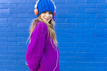 Portrait of smiling girl with headphones wearing blue cap and  pink pullover in front of blue wall - ERRF01212