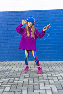 Singing girl dancing in front of blue wall while listening music with headphones - ERRF01215