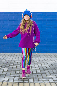 Happy girl dancing in front of blue wall while listening music with headphones and smartphone - ERRF01218