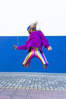 Girl listening music with headphones and smartphone jumping in the air - ERRF01221