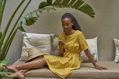 Relaxed young woman sitting on a couch checking her phone - VEGF00099