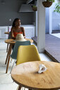 Young woman sitting at tablein a cafe looking sideways - VEGF00114