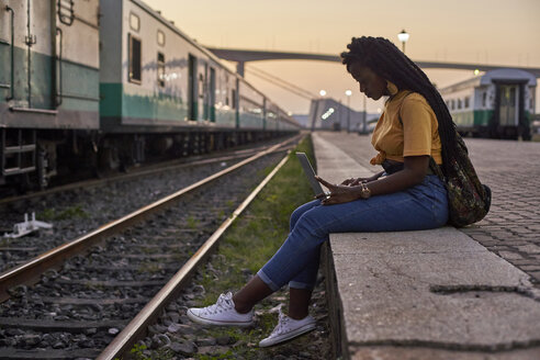 Young woman sitting on platform at the train station using laptop - VEGF00120