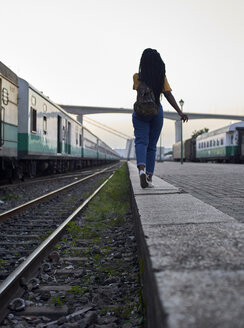Rear view of young woman walking at the edge of the rail at the train station - VEGF00135