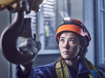Young female industrial worker with safety helmet taking hook of indoor crane - CVF01123
