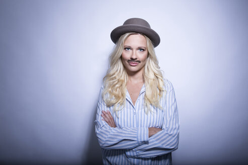 Portrait of blond young woman with fake moustache and hat crossing arms - MFRF01298