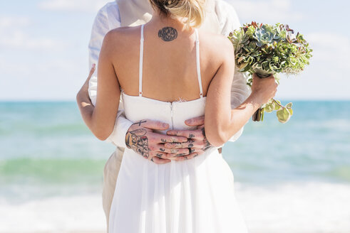 Caucasian bride and groom with tattoos hugging on beach - BLEF01857
