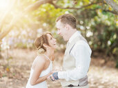 Caucasian bride and groom laughing outdoors - BLEF01860