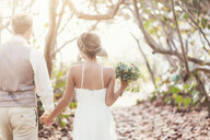 Caucasian bride and groom holding hands outdoors - BLEF01863