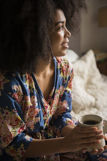African American woman sitting in bed drinking coffee - BLEF01947