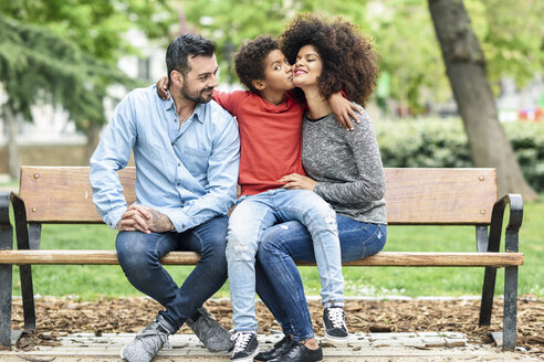 Spain, Madrid, Madrid. Multiracial family siiting together on a bench with a son kissing his mother in an urban park. Lifestyle concept. - JSMF01051
