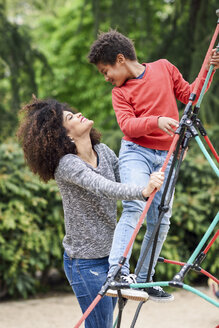 Spain, Madrid, Madrid. Happy black boy, seven years old, playing outdoors with his mother in an urban park playground. Lifestyle concept. - JSMF01063