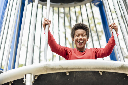 Spain, Madrid, Madrid. Happy black boy, seven years old, playing outdoors in an urban park playground. Lifestyle concept. - JSMF01066