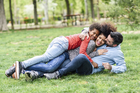 Spain, Madrid, Madrid. Multiracial family having fun lying together on the grass in an urban park. Lifestyle concept. - JSMF01069