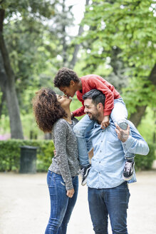 Father carrying son piggyback in a park, while son is kissing his mother - JSMF01072