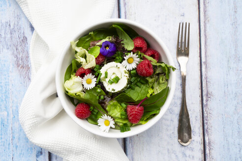 Bowl of leaf salad with raspberries and cream cheese garnished with edible flowers - LVF07998