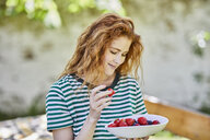 Portrait of smiling redheaded young woman with bowl of berries in the garden - FMKF05662
