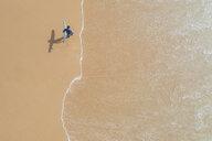 Portugal, Algarve, Sagres, Praia da Mareta, aerial view of man carrying surfboard on the beach - MMAF00900