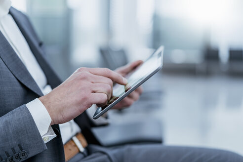 Close-upof businessman sitting in waiting area using tablet - DIGF06831