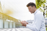 Businessman using tablet outside in the city - DIGF06849